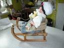 świąteczna lalka porcelanowa w sanich z misiem