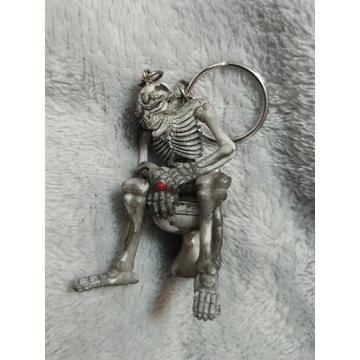 Breloczek szkielet z papierosem na sedesie