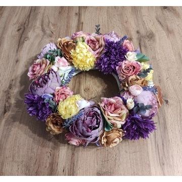 Kompozycja kwiatowa na wiklinowym kole.