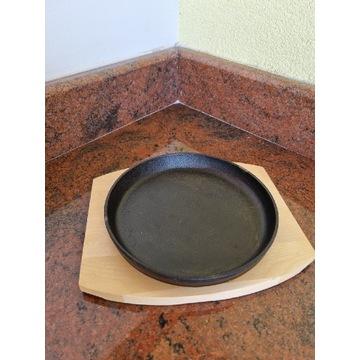 Gorący zeliwny talerz z drewniana podstawką
